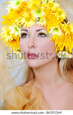 Portrait of beautiful woman with stylish makeup and yellow flowers around her
