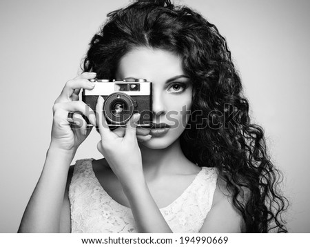Portrait of beautiful woman with the camera. Girl photographer. Fashion photo