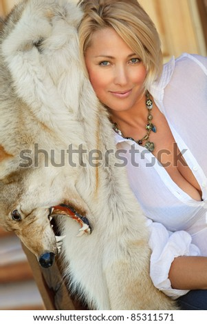 Portrait of  beautiful woman with wolf skin - stock photo