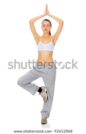 portrait of beautiful woman working out yoga exercise (tree pose), isolated on white background - stock photo
