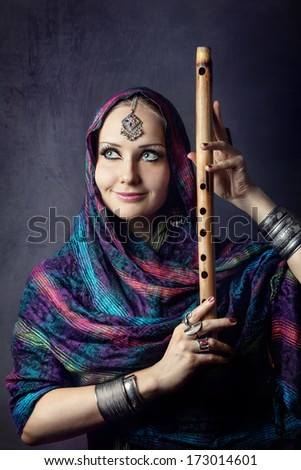 Portrait of beautiful woman wrapped in scarf holding bamboo bansuri Indian flute - stock photo
