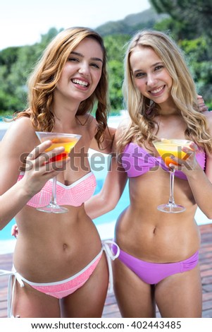Portrait of beautiful women in bikini holding a cocktail glass near the pool - stock photo