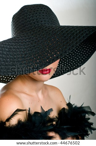 Portrait of beautiful women in black hat and boa - stock photo