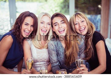 Portrait of beautiful women smiling and having drinks at the party - stock photo