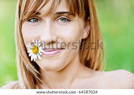 Portrait of beautiful young adult holding flower in mouth, against green summer nature. - stock photo