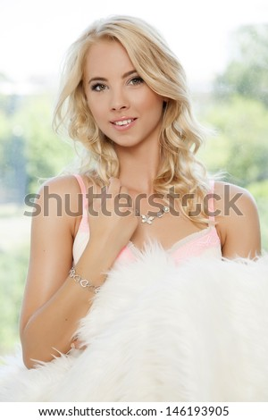 portrait of beautiful young adult sensual blonde babe girl wrapped in white fur