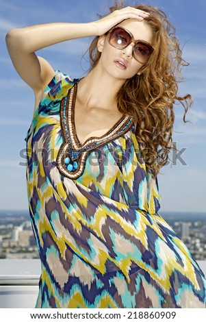 portrait of beautiful young adult sensuality and attractive pretty brunette woman in fashionable sunglasses on background blue sky - stock photo