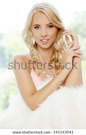 portrait of beautiful young adult sensuality blonde woman wrapped in white fur