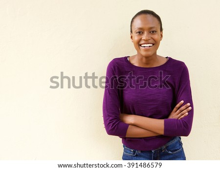 Portrait of beautiful young african american woman smiling with arms crossed  - stock photo