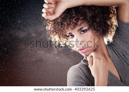 Portrait of beautiful young African American woman with afro and glamour makeup. Studio shot. - stock photo