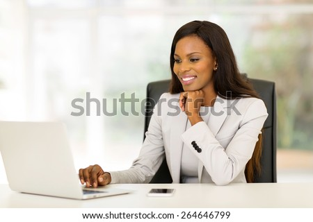 portrait of beautiful young african business woman in office - stock photo