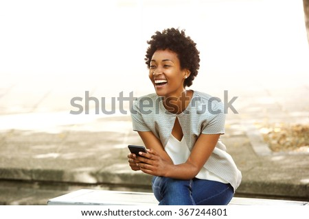 Portrait of beautiful young african woman smiling while sitting outside on a bench holding mobile phone - stock photo