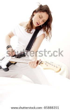 Portrait of beautiful young and attractive woman playing her guitar at home - stock photo