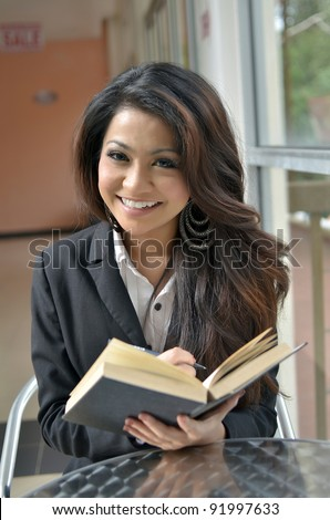 Portrait of beautiful young Asian business woman reading a book with lovely smile - stock photo