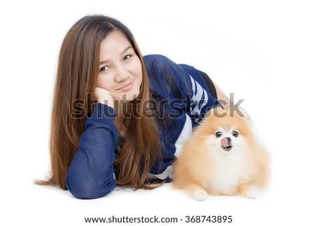Portrait of Beautiful young Asian girl hugging a nice cute Pomeranian dog - stock photo