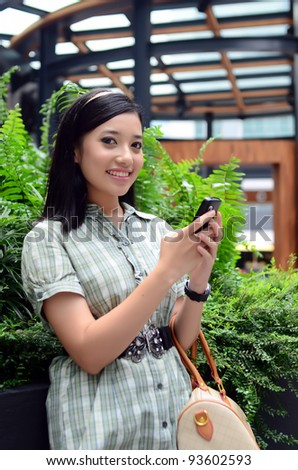 Portrait of beautiful young Asian Muslim business woman texting on her cell phone