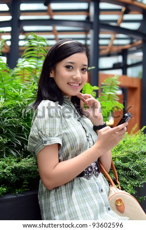 Portrait of beautiful young Asian Muslim business woman texting on her phone outdoor - stock photo