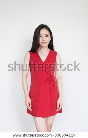 Portrait of beautiful young Asian woman in red dress - stock photo