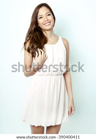 portrait of beautiful young asian woman with flawless skin and perfect make-up wearing pink spring dress - stock photo