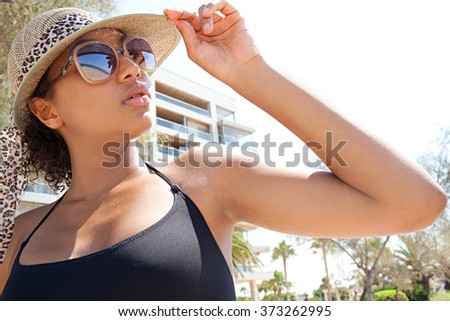 Portrait of beautiful young black woman in a summer holiday hotel resort with sunglasses with beach reflections, holding the beam of straw hat, sunbathing by sea, outdoors. Luxury lifestyle exterior. - stock photo