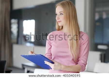 Portrait of beautiful young blond businesswoman  writing notes while standing at office.  - stock photo
