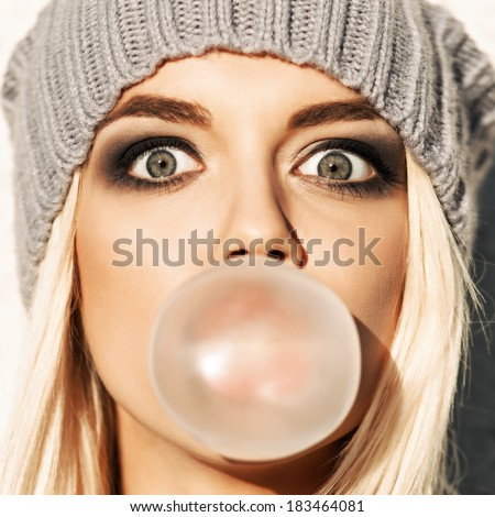 Portrait of beautiful young blond girl in beanie hat blows big bubble from bubble gum - stock photo