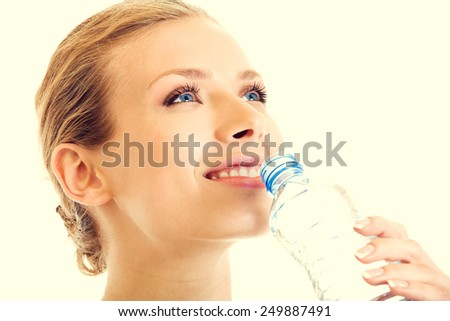 Portrait of beautiful young blond woman drinking water - stock photo