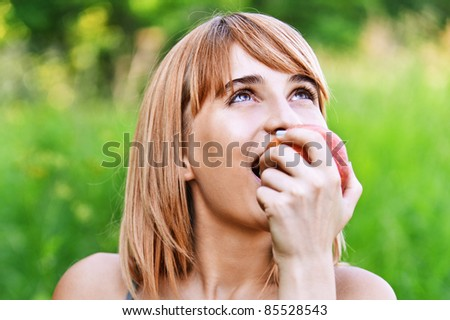 portrait of beautiful young blond woman eating fresh red apple at park - stock photo