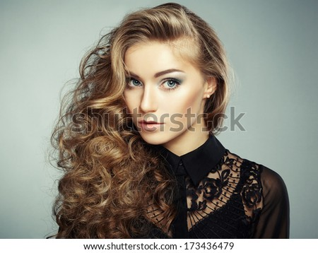 Portrait of beautiful young blonde girl in black dress - stock photo