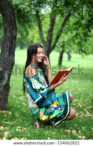Portrait of beautiful young blonde girl reading a book in the park