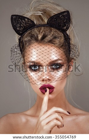 portrait of beautiful young blonde girls, with glowing skin, beautiful makeup and very puffy kissable lips,with cat ears on her head and veil, the netting on face with professional retouching - stock photo