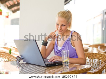 Portrait of beautiful young blonde woman being happy about findings through her laptop - stock photo