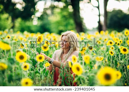 portrait of beautiful young blonde woman grabbing sunflower and smiling - stock photo