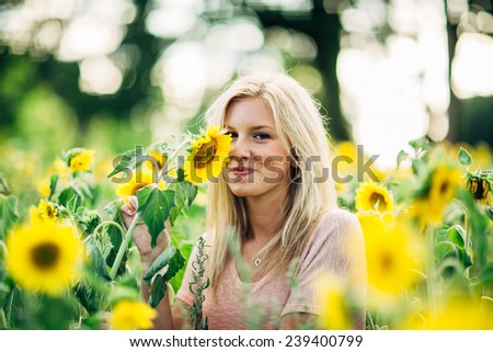 portrait of beautiful young blonde woman grabbing sunflower smelling sunflower looking at camera smiling - stock photo