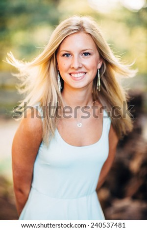 portrait of beautiful young blonde woman hair blowing in wind - stock photo