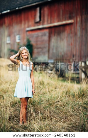 portrait of beautiful young blonde woman in tall grass holding in front of barn holding hair variation - stock photo