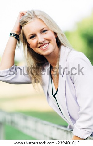 portrait of beautiful young blonde woman leaning over fence smiling grabbing hair - stock photo