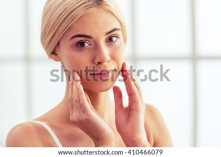 Portrait of beautiful young blonde woman looking at camera and touching her face - stock photo