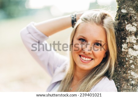 portrait of beautiful young blonde woman outside sitting by tree close up - stock photo