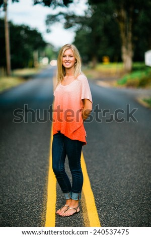 portrait of beautiful young blonde woman standing in road arms behind back - stock photo
