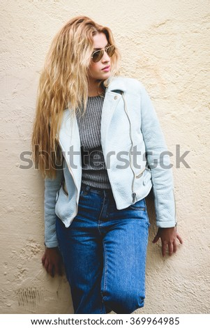 Portrait of beautiful young blonde woman with  curly hair. Girl wearing leather jacket, blue jeans and aviator sunglasses in urban background. - stock photo