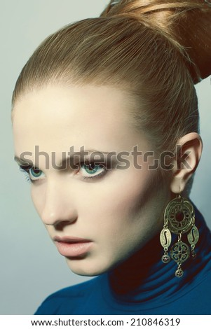 Portrait of beautiful young blue-eyed blonde wearing blue dress and ethnic golden earrings. Model posing over light-blue background. Perfect skin, make-up and stylish hairdo. Retro style. Studio shot