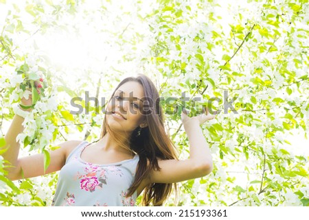 portrait of beautiful young brown hair woman standing near the apple tree on a warm summer sunny day against sun light sky background Copy space for inscription - stock photo