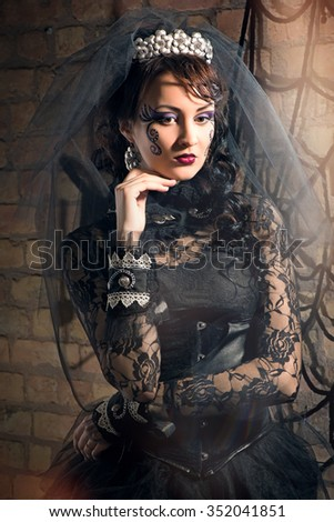Portrait of beautiful young brunette girl in black dress and veil in the Gothic style