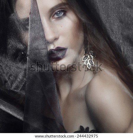 Portrait of beautiful young brunette girl in the studio with a veil in the Gothic style, closeup - stock photo