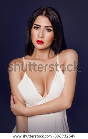 Portrait of beautiful young brunette girl in white dress in studio - stock photo