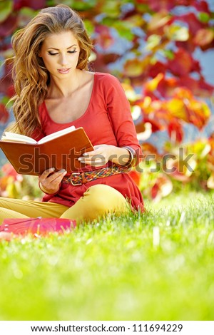 Portrait of beautiful young brunette girl reading a book in the park at fall. - stock photo