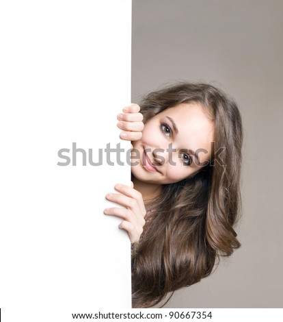 Portrait of beautiful young brunette with blank board. - stock photo