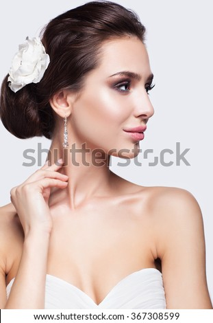 Portrait of beautiful young brunette woman bride in white Wedding Dress on light gray background - stock photo
