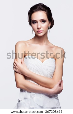 Portrait of beautiful young brunette woman bride in white Wedding Dress with hands crossed on light gray background